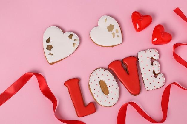 Zelfgemaakte peperkoek met letters liefde voor valentijnsdag gelegen op een roze