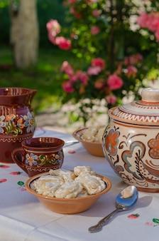 Zelfgemaakte pierogi in klei etnische oekraïense gerechten op een tafel in de zomertuin.
