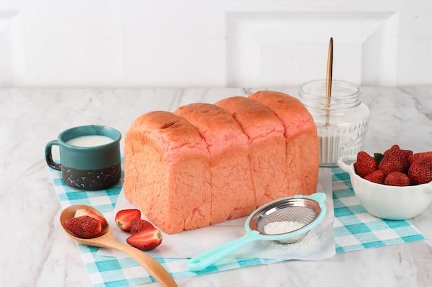 Zelfgemaakte pink loaf aardbeienbrood voor sandwich ontbijt. geserveerd met melk en verse aardbeien. kopieer ruimte voor tekst of advertentie