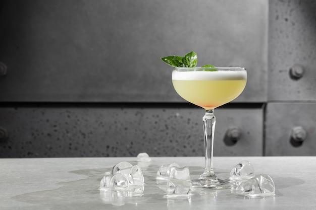Zelfgemaakte pisco zure cocktail. whiskey sour in coupe glass met ijs op grijs