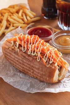 Zelfgemaakte pittige hotdog met koreaanse wortelen, kool, mosterd en pikante saus