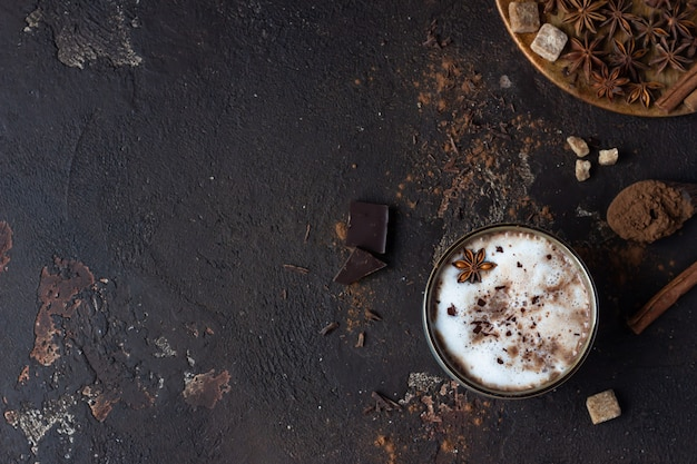Zelfgemaakte pittige warme chocolademelk met anijsster, kaneelstokjes en bittere chocolade