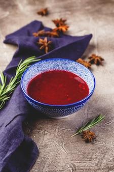 Zelfgemaakte pittige zoete saus van bosbessen, veenbessen en appels met rozemarijn, kaneel en anijssterren in blauwe kom.
