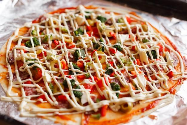 Zelfgemaakte pizza bereiden om te koken.