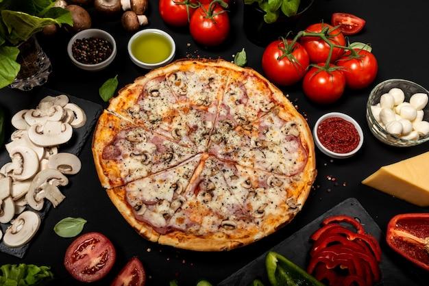 Zelfgemaakte pizza klaar om te eten met rauwe ingrediënten. bovenaanzicht