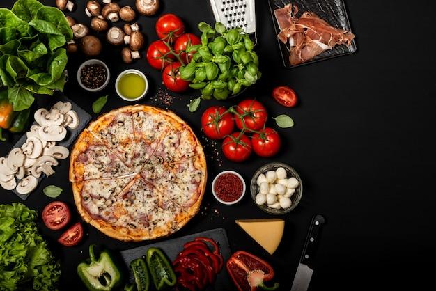 Zelfgemaakte pizza klaar om te eten met rauwe ingrediënten.