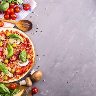 Zelfgemaakte pizza maken van deeg met champignons, tomaten en kaas