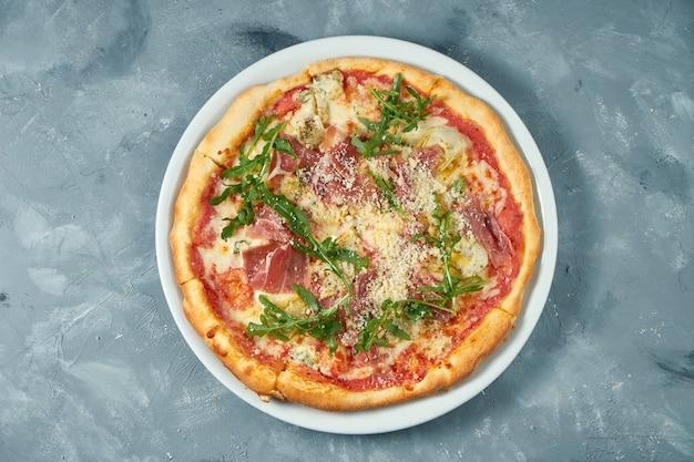 Zelfgemaakte pizza met jamon, rucola en parmezaanse kaas in een witte plaat op een betonnen ondergrond. detailopname. selectieve aandacht