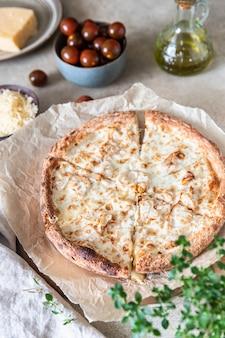 Zelfgemaakte pizza met kip en kaas op een lichte betonnen ondergrond met witte saus