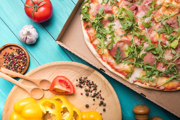 Zelfgemaakte pizza met paprika; tomaten knoflook en specerijen op houten tafel