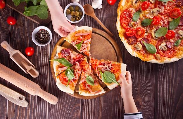 Zelfgemaakte pizza met peperoniworst, spek verfraaide spinazie en ingrediënten op de achtergrond. bovenaanzicht. de hand van kinderen neemt een stuk.