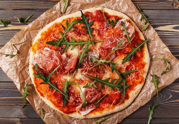 Zelfgemaakte pizza met prosciutto en rucola.