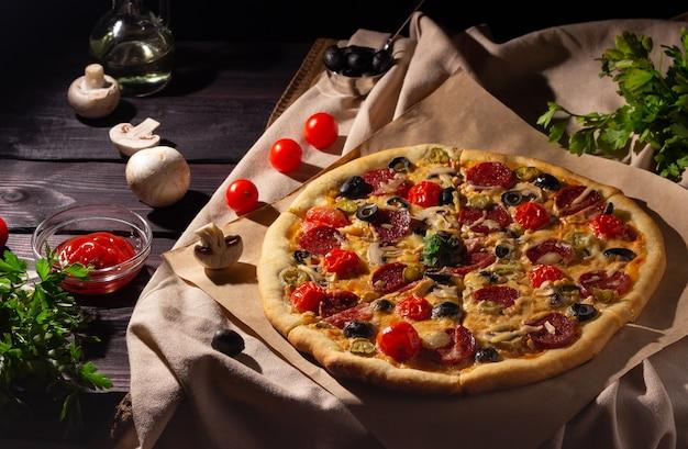 Zelfgemaakte pizza met salami, champignons en cherrytomaatjes op een donkere achtergrond. zijaanzicht.