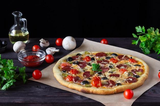 Zelfgemaakte pizza met salami, champignons en kerstomaatjes op een donkere achtergrond. zijaanzicht.
