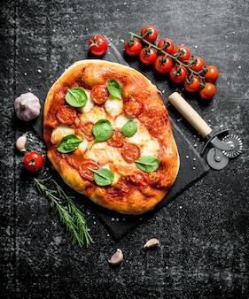 Zelfgemaakte pizza met tomaten op een tak en rozemarijn. op donkere rustieke ondergrond
