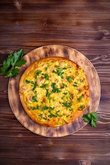 Zelfgemaakte pizza met vlees en kaas en groenten op een houten tafel. kopieer ruimte bovenaanzicht