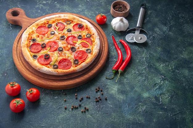Zelfgemaakte pizza op houten snijplank en peper knoflook tomaten op donkere ondergrond