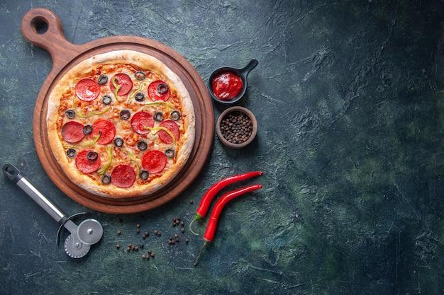 Zelfgemaakte pizza op houten snijplank en peperketchup aan de rechterkant op geïsoleerd donker oppervlak