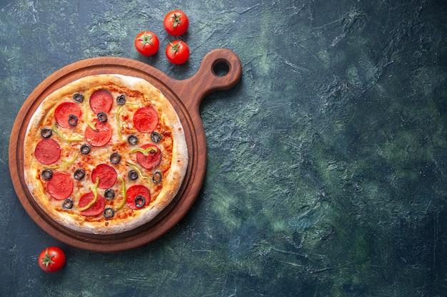 Zelfgemaakte pizza op houten snijplank en tomaten op geïsoleerde donkere ondergrond