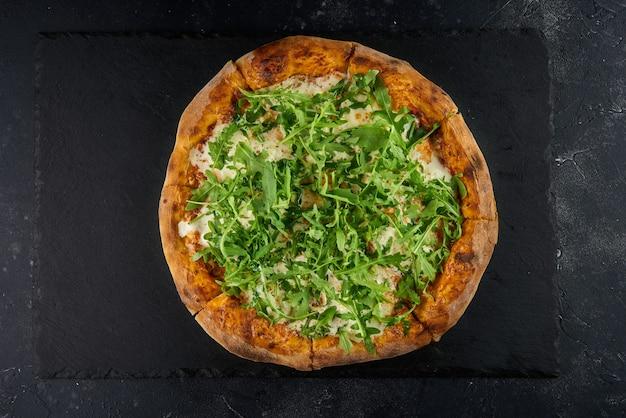 Zelfgemaakte pizza versierd met verse rucola op een donkere leiachtergrond, bovenaanzicht
