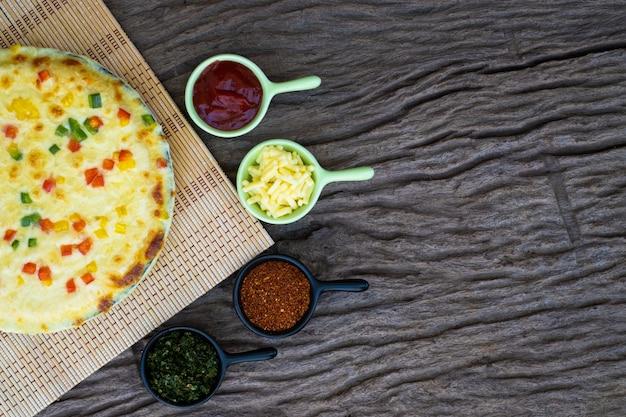 Zelfgemaakte plantaardige pizza met kerstomaatjes en andere ingrediënten op een houten achtergrond