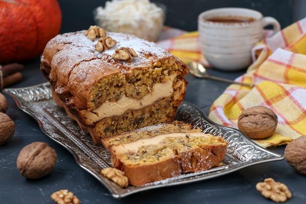 Zelfgemaakte pompoen muffin met kwark en walnoten, bestrooid met poedersuiker en kopje thee tegen een donkere ondergrond, selectieve aandacht