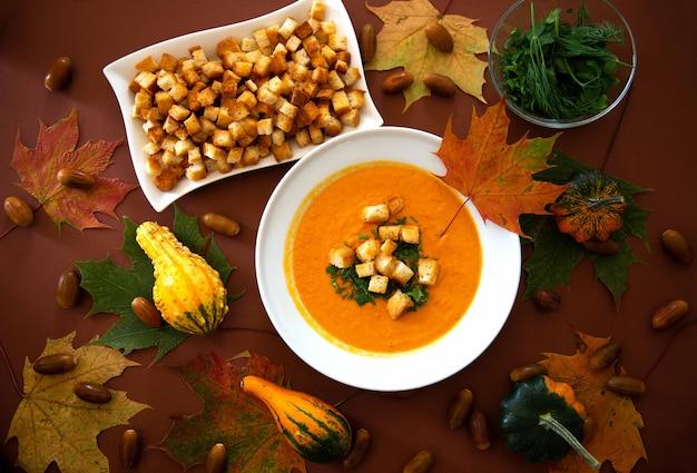 Zelfgemaakte pompoensoep met room en crackers op herfstbladeren