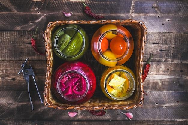 Zelfgemaakte potten van ingemaakte verse komkommers, sappige tomaten, zoete courgette in een rieten doos op een houten achtergrond.