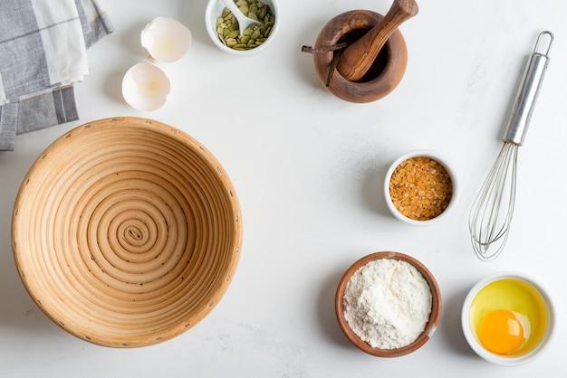 Zelfgemaakte productie van vers gezond brood van andere gebak uit natuurlijke ingrediënten op een lichtgrijze tafel.