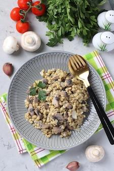 Zelfgemaakte ptitim pasta met champignons in een plaat op lichtgrijze tafel. verticaal formaat. uitzicht van boven