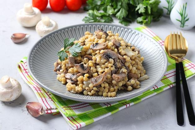 Zelfgemaakte ptitim pasta met champignons in een plaat op lichtgrijze tafel.