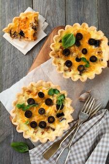 Zelfgemaakte quiche taart met kip, aubergine, olijven en kaas op oude houten oppervlak. selectieve aandacht.