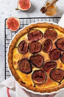Zelfgemaakte quiche taart met vijgen, roomkaas en honing op lichte houten achtergrond. vintage-stijl. bovenaanzicht