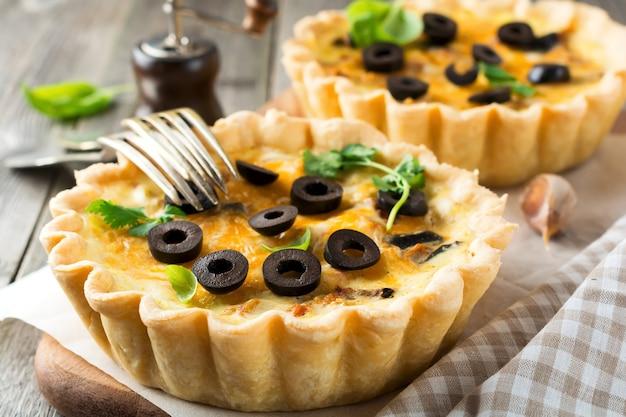 Zelfgemaakte quichetaart met kip, aubergine, olijven en kaas op oude houten ondergrond. selectieve aandacht.