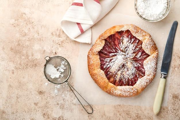Zelfgemaakte rabarber galette gemaakt met sterpatroon op oude betonnen tafel achtergrond. proces van bakken. taart openen. kerstmis en nieuwjaar gebakken goederen. bovenaanzicht van zelfgemaakte taartbodem op tafel.