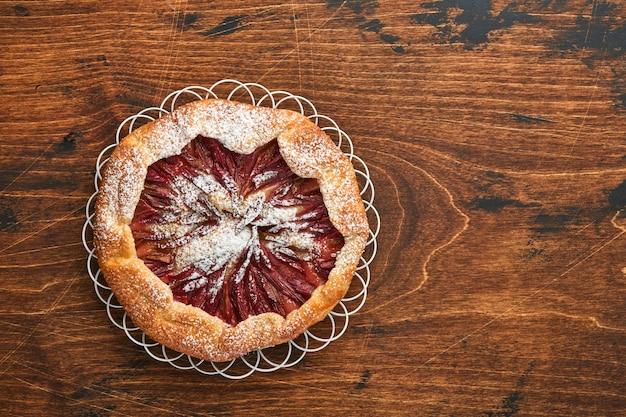 Zelfgemaakte rabarber galette gemaakt met sterpatroon op oude houten tafel achtergrond. proces van bakken. taart openen. kerstmis en nieuwjaar gebakken goederen. bovenaanzicht van zelfgemaakte taartbodem op tafel.
