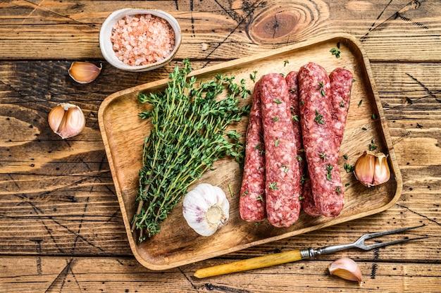 Zelfgemaakte rauwe gehakt vlees worstjes op een snijplank