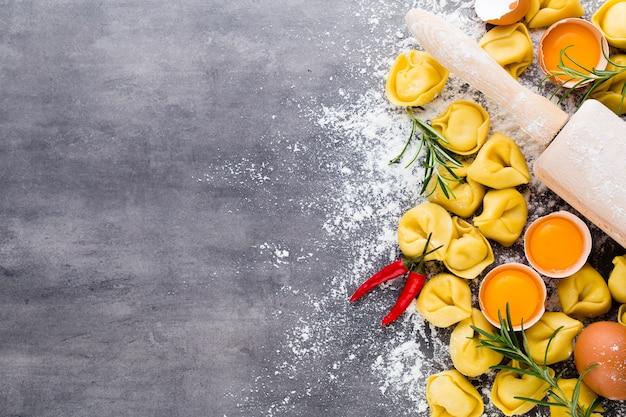 Zelfgemaakte rauwe italiaanse tortellini en basilicumblaadjes.