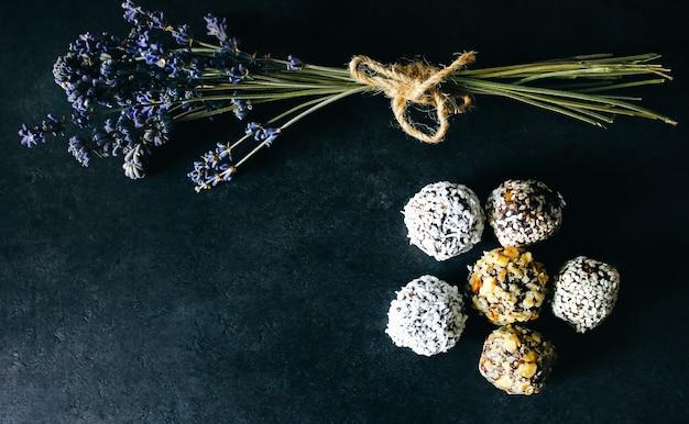Zelfgemaakte rauwe truffels met cacao, noten, kokos en dadels op grijze tafel. lavendel boeket op achtergrond. veganistisch, biologisch en gezond snoepgoed. provençaalse stijl.