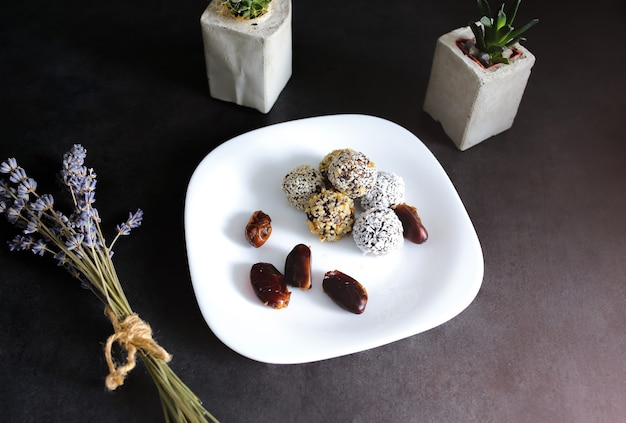 Zelfgemaakte rauwe truffels met cacao, noten, kokos en dadels op witte plaat en grijze tafel. lavendel en vetplanten in betonnen vazen op de achtergrond. veganistisch, biologisch en gezond snoepgoed.