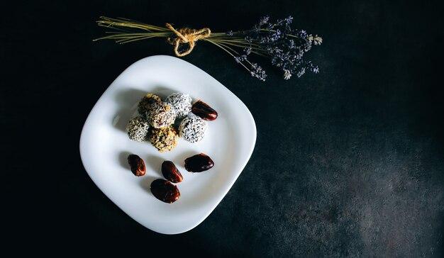 Zelfgemaakte rauwe truffels met cacao, noten, kokos en dadels op witte plaat en grijze tafel. lavendel op achtergrond. veganistisch, biologisch en gezond snoepgoed.