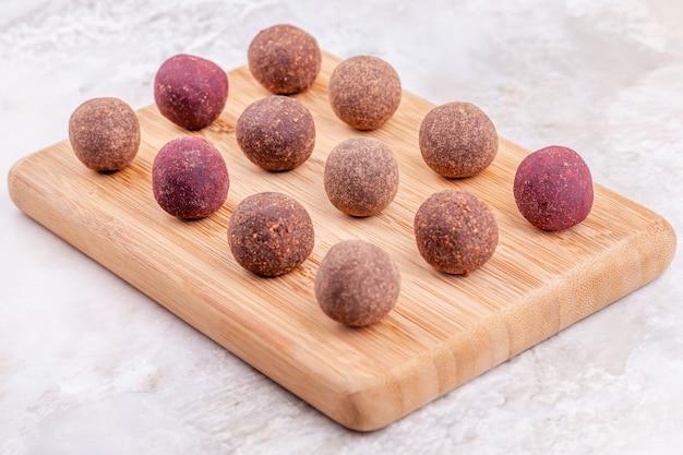 Zelfgemaakte raw vegan cacao energie ballen op houten dienblad