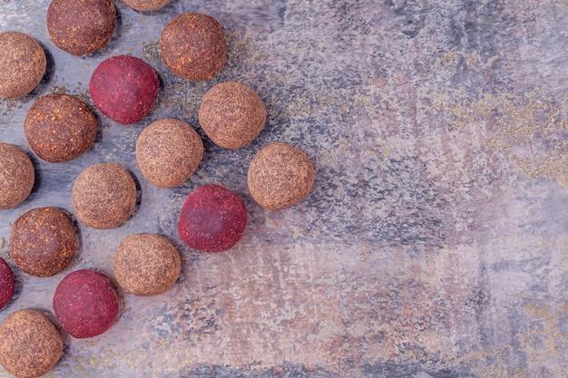Zelfgemaakte raw vegan cacao energy balls liggen op een rij op grijze tafel