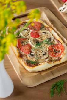 Zelfgemaakte rechthoekige pizza margherita met champignons op een houten bord