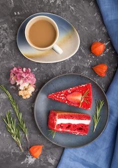 Zelfgemaakte red velvet cake met melkroom en aardbei met kopje koffie op een zwarte betonnen ondergrond met blauw textiel