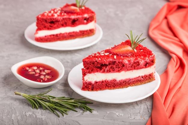 Zelfgemaakte rode fluwelen cake met melkroom en aardbei op een grijze betonnen ondergrond met rode textiel