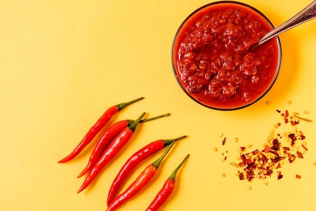 Zelfgemaakte rode harissa-pasta, chilipepers en verse rode chilipepers.
