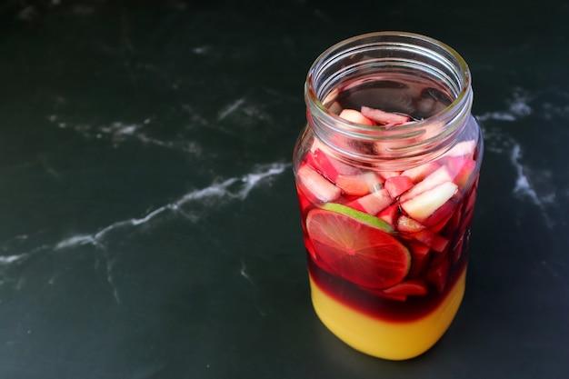 Zelfgemaakte rode wijn sangria voor het mengen geïsoleerd op zwart marmeren tafel