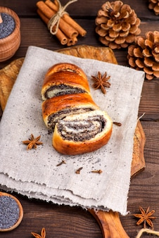 Zelfgemaakte roll met maanzaad op een bruin houten bord
