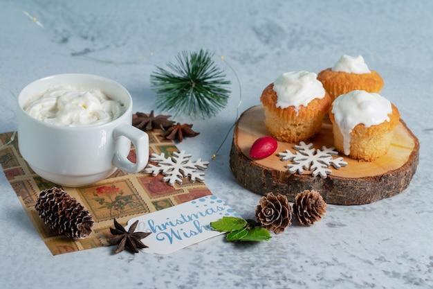 Zelfgemaakte romige muffins op houten oppervlak met warme chocolademelk.